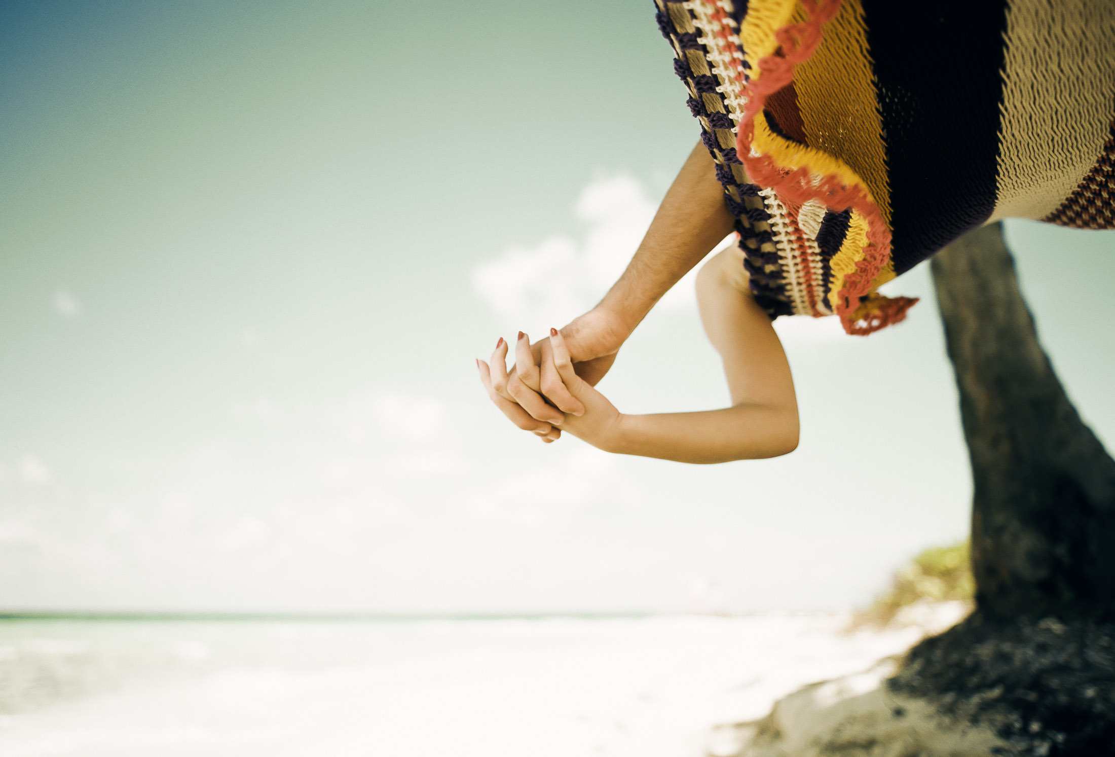 Hands intertwined on beach